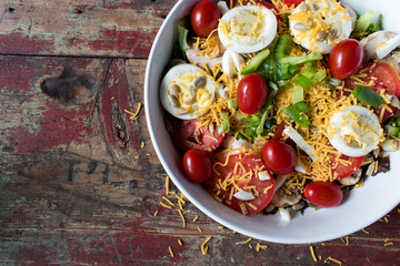 garden salad with tomatoes, cheese, and eggs top view closeup