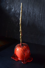 red candy apple with black sugar on dark rustic background