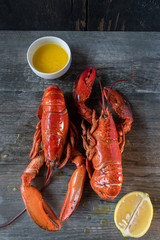 two cooked red lobsters with butter and lemon top view