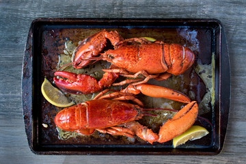 two cooked red lobsters in rustic setting top view