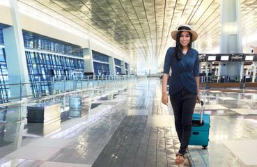 Beautiful asian woman walking while pulling blue suitcase