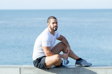 Pensive Strong Sporty Man Sitting on Parapet at Sea