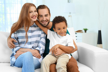 Happy couple with adopted African-American boy sitting on couch at home