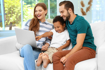 Happy couple with adopted African-American boy using laptop while sitting on couch at home