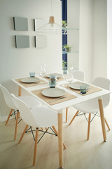 Interior of light modern dining room with served table