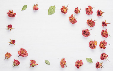 Dried roses flowers on vintage wooden table