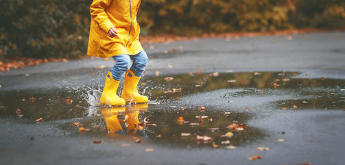 legs of child in yellow rubber boots in  puddle in autumn.
