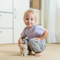 Toddler kid boy playing with cat kitten in children room