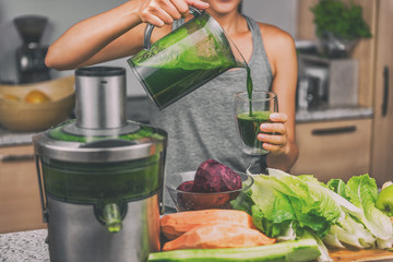 Poster Juice Woman juicing making green juice with juice machine in home kitchen. Healthy detox vegan diet with vegetable cold pressed extractor to extract nutrients for smoothie drink.