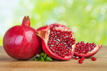 pomegranates whole and cut on wooden table