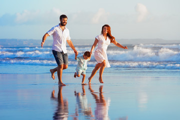 Happy family - father, mother, baby son have fun together, child run with splashes by water pool along sunset sea surf on black sand beach. Travel lifestyle, parents with kids on summer vacation.