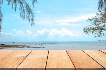 Empty wooden table with blur beach on background