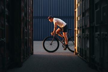 Radfahrer mit einem Fixie bei Sonnenuntergang im Container Hafen
