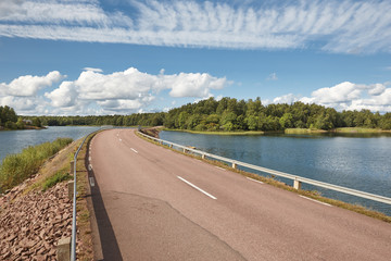 Finnish landscape with road, lake and forest island. Finland
