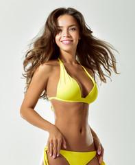 Sexy young brunette woman posing in a bikini.Beautiful perfect figure. Studio portrait.