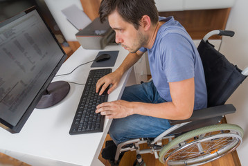 Handicapped disabled man on wheelchair is working with computer in office.