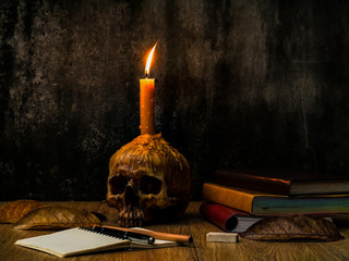 A wizard working desk with candle on the human skull, books of magic, note book and stationary.