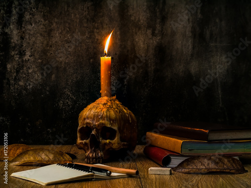A wizard working desk with candle on the human skull, books