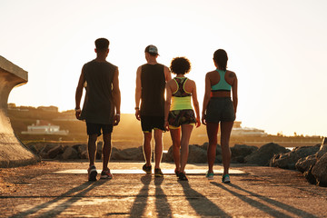 Full length back view image of fitness people walking outdoors