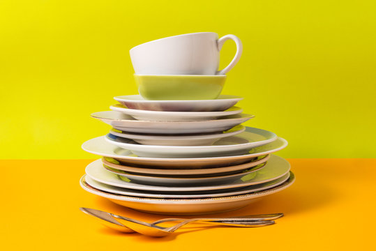 Stack of plates, dishware on colorful background.