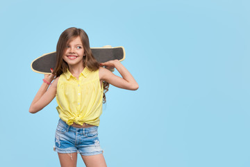 Smiling girl holding cruiser board posing