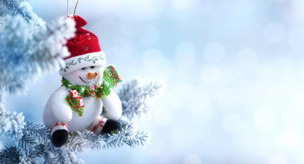 Background of Christmas Snowman Hanging on a Snow Tree Branch