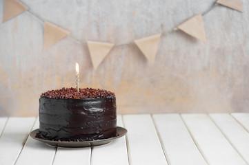 Chocolate birthday cake with burning candle