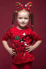 Funny little girl in the New Year's image, showing different emotions. Photo taken in studio