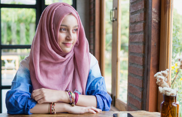 Portrait of muslim girl sitting in the coffee shop.