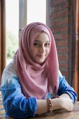 Portrait of muslim girl sitting in the coffee shop.