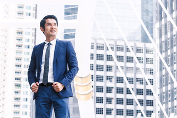 Portrait of handsome man in blue suit standing outdoors
