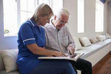 Senior man sitting looking at photo album  with care nurse