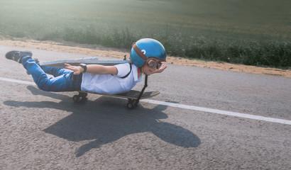Little boy wearing helmet and styrofoam wings riding skateboard on a rural road, pretending to be a pilot