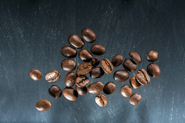 Group of flying coffee beans on black background.