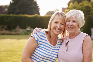 Senior woman and adult daughter embracing in garden