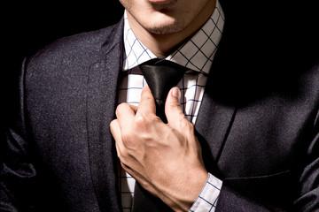 Businessman adjusting his suit on black background