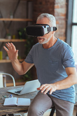 Curious aged man testing vr glasses at home