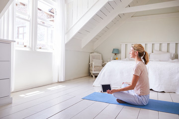 Woman With Digital Tablet Using Meditation App In Bedroom