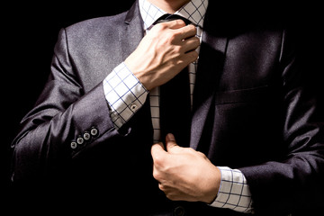Businessman adjusting his suit on black background