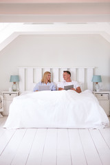 Couple Wearing Pajamas Lying In Bed Using Digital Devices