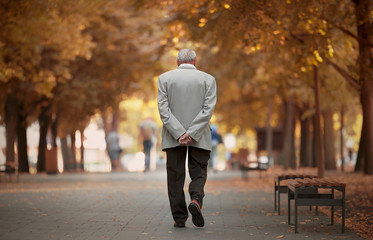 Old man walking in autumn park