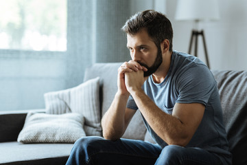 Unhappy bearded man sitting on the sofa