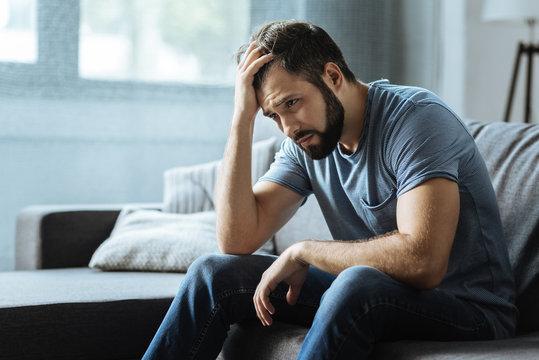 Sad gloomy man holding his forehead