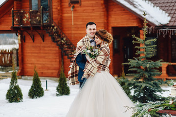 Winter wedding outdoors on background of snow-covered house. Bride and groom are standing and hugging.