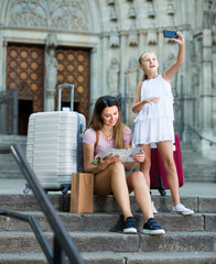 Girl making selfie with phone during traveling with mother