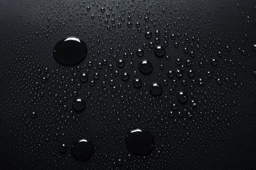 Close-up of raindrops on black surface