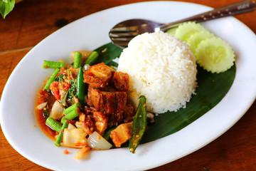 crispy pork with spicy sauce over Rice.