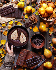 Chocolate Brownie with a pear in a baking dish is hold by a female hand in a sweater. Food gathering style. Autumn background. Ingredients for its preparation. Flat lay instagram food composition.