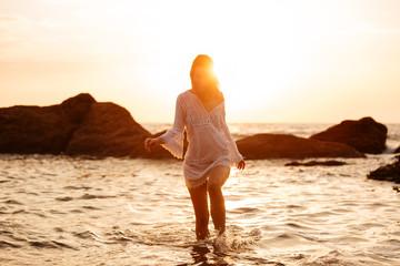 Cheerful brunette woman in light summer dress walking in sea