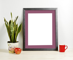 Frame mockup with plant pot, mug and apple on wooden shelf
